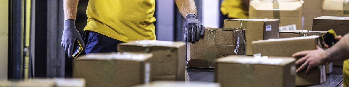 Unrecognisable delivery warehouse workers handling packages on conveyor belt.